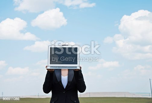 Businesswoman holding a laptop outdoors