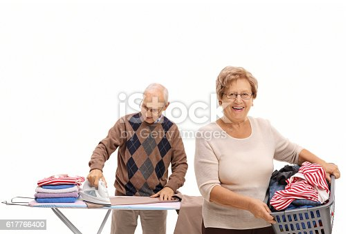 802472024istockphoto Woman holding a laundry basket and a man ironing 617766400