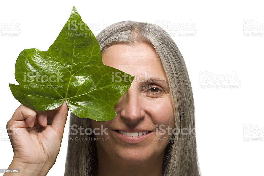 Woman holding a leaf to face stock photo