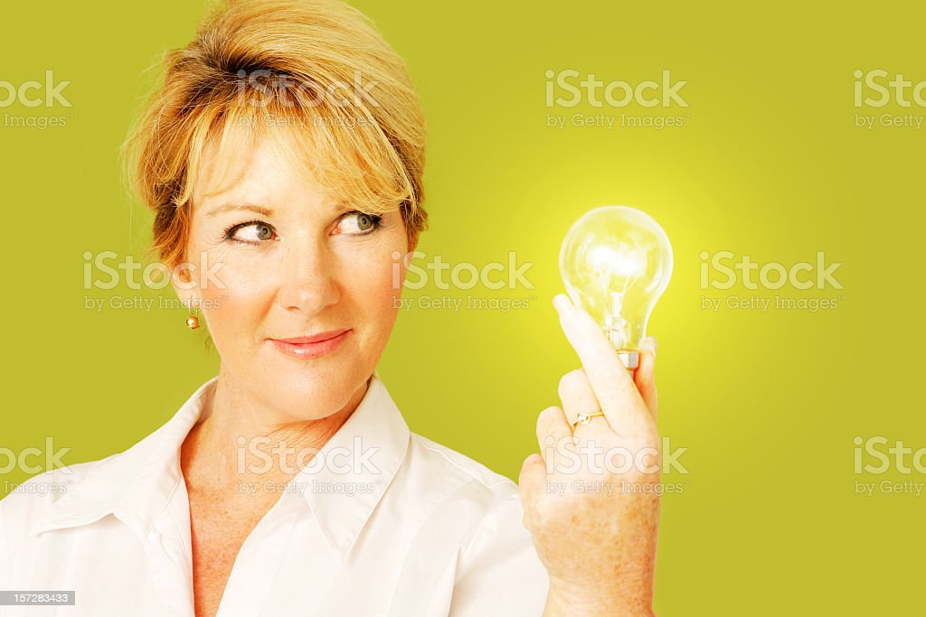 Woman holding a lit light bulb on bright yellow background royalty-free stock photo
