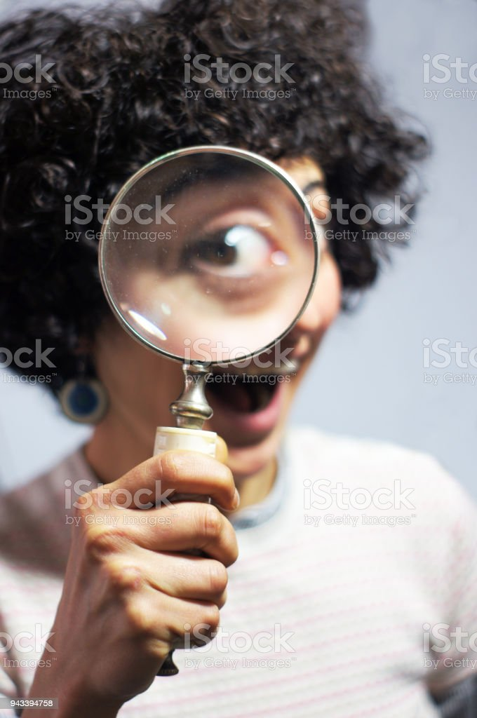Woman holding and looking through a magnifier