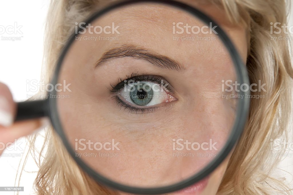woman holding a magnifying glass up to her eye royalty-free stock photo
