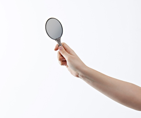 Woman holding a handheld make up mirror