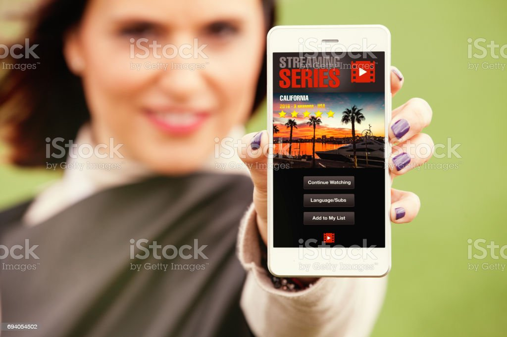 Woman holding a mobile phone in the hand with streaming video app in the screen. stock photo