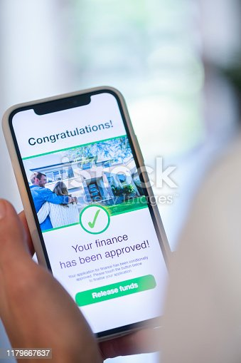 istock Woman holding a mobile phone with loan application approval. 1179667637