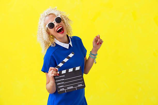 woman holding a movie directors scene card - film oder fernsehvorführung stock-fotos und bilder