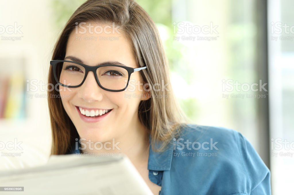 Woman holding a newspaper wearing eyeglasses looking at you stock photo