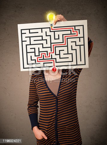 istock Woman holding a paper with a labyrinth on it in front of her head 1196024221