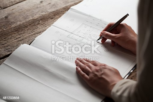 536971177 istock photo woman holding a pen over a house constructing plan 481203858