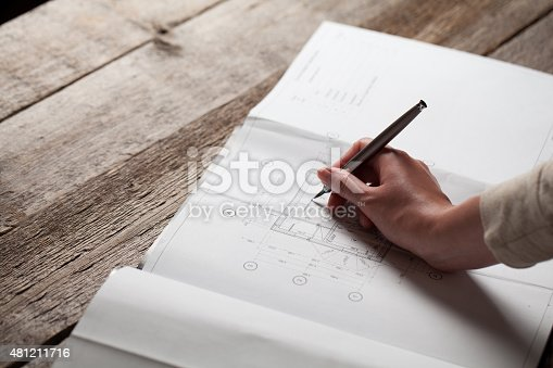 536971177 istock photo woman holding a pen over a house constructing plan 481211716