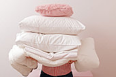 Woman holding a pile of bedding for sleeping. Household