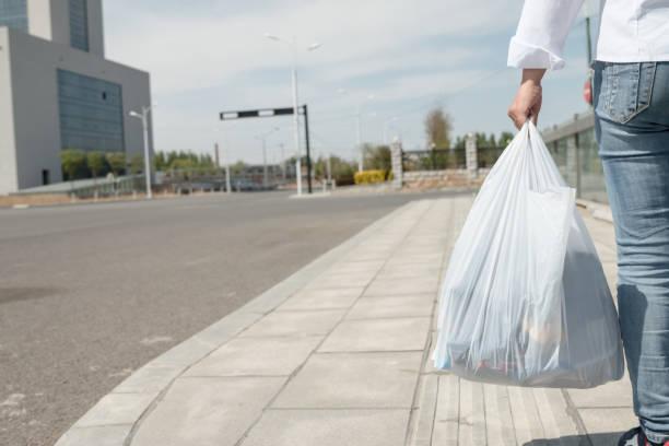 woman holding a plastic bag - sac en plastique photos et images de collection