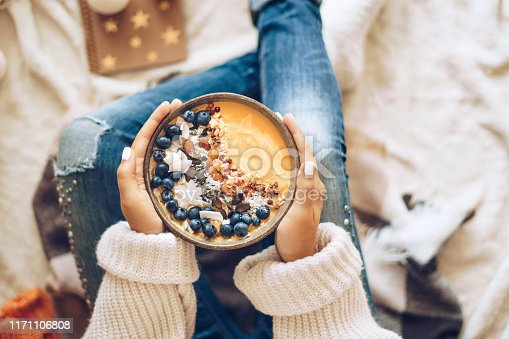 Pumpkin pie smoothie bowl topped with berries, granola, and coconut flakes