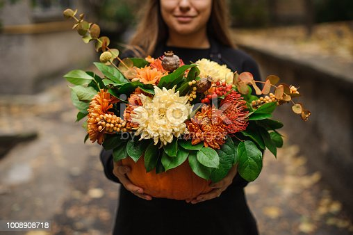 Smiling woman in black dress holding a beautiful pumpkin with beautiful autumn flowers on the outdoors background