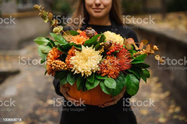 Photo of Woman holding a pumpkin with autumn flowers