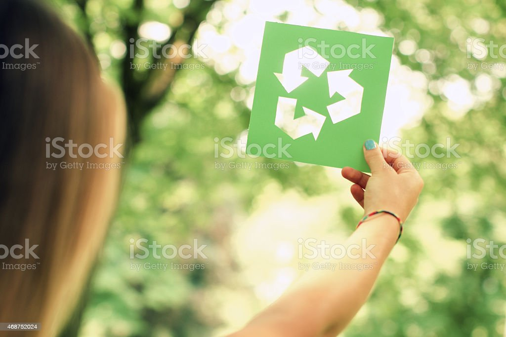 Woman holding a recycle sign stock photo