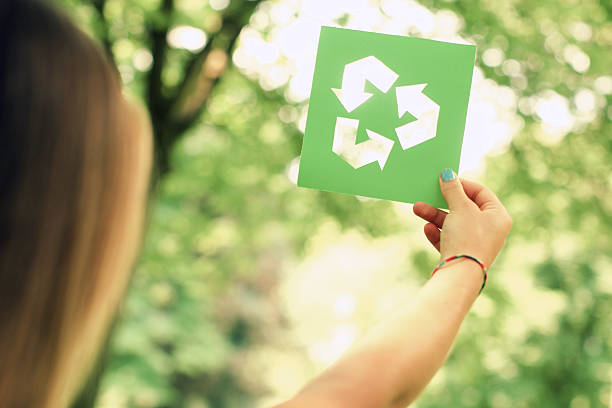 woman holding a recycle sign - recycling symbol stock photos and pictures