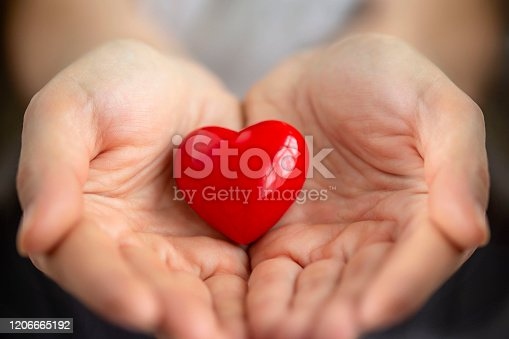 Close-up shot of woman holding a red heart in her hands.