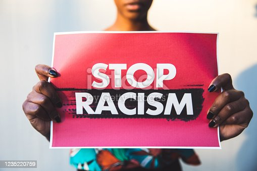 Woman holding a red sign agains racism