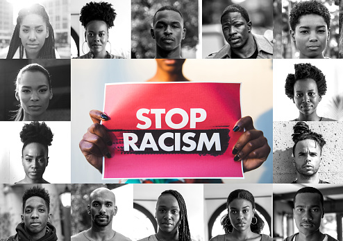 Woman holding a red sign against racism and a mix of afro american men and women faces.