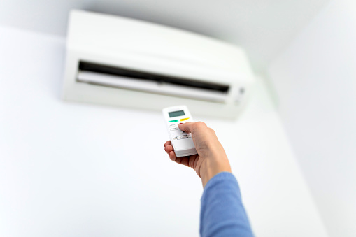 istock Woman holding a remote of a modern airconditioner unit at home. 1207721829