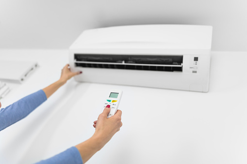istock Woman holding a remote of a modern airconditioner unit at home. 1207722436