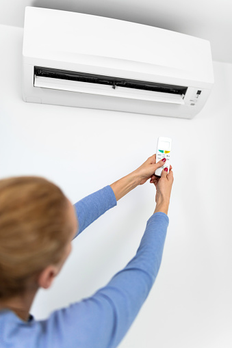 istock Woman holding a remote of a modern airconditioner unit at home. 1208758948
