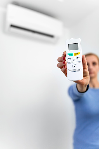 istock Woman holding a remote of a modern airconditioner unit at home. 1210994476