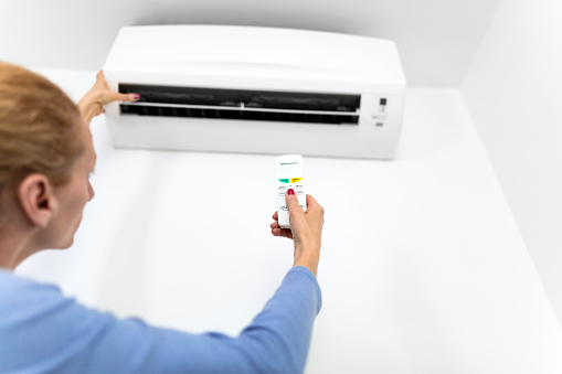 istock Woman holding a remote of a modern airconditioner unit at home. 1213004576