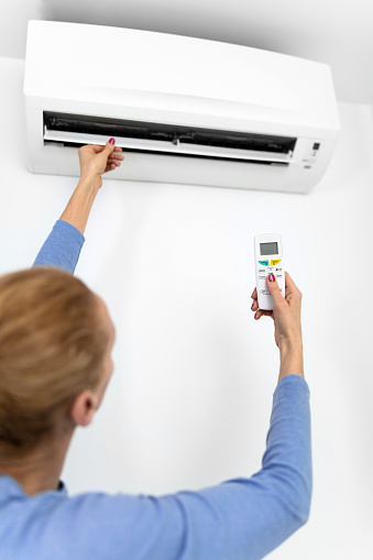 istock Woman holding a remote of a modern airconditioner unit at home. 1213004680