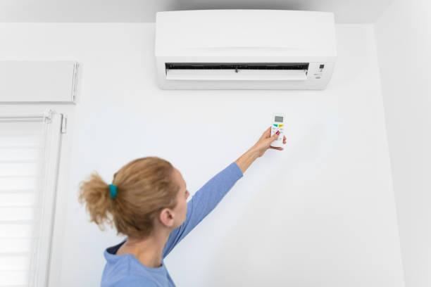 Frau hält eine Fernbedienung einer modernen Klimaanlage Einheit zu Hause. – Foto