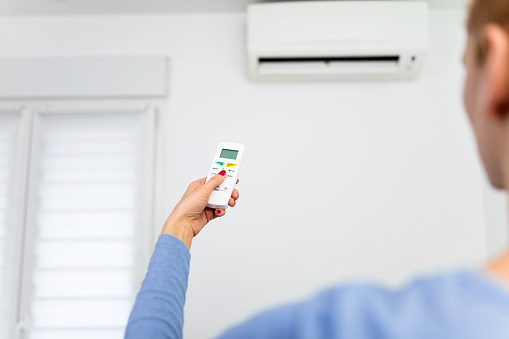 istock Woman holding a remote of a modern airconditioner unit at home. 1216212445