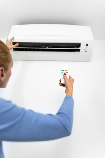 istock Woman holding a remote of a modern airconditioner unit at home. 1217110386