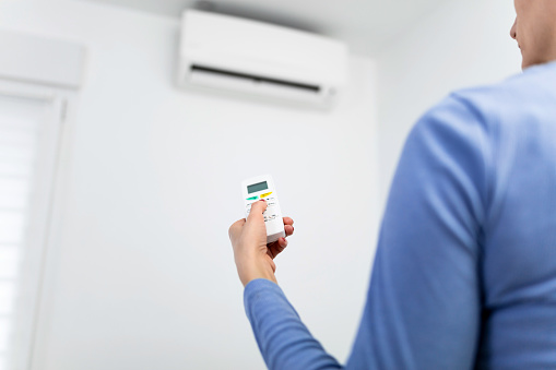 istock Woman holding a remote of a modern airconditioner unit at home. 1218502118