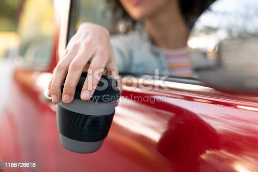 Young woman driving through Argentina on a Road Trip. Here using a travel mug in the car, holding in out the window.