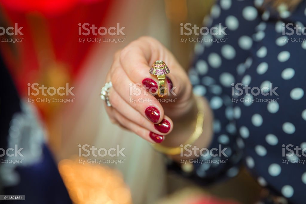 Woman holding a ring in his hand, picture has a shallow depth of field so his face is not recognizable stock photo