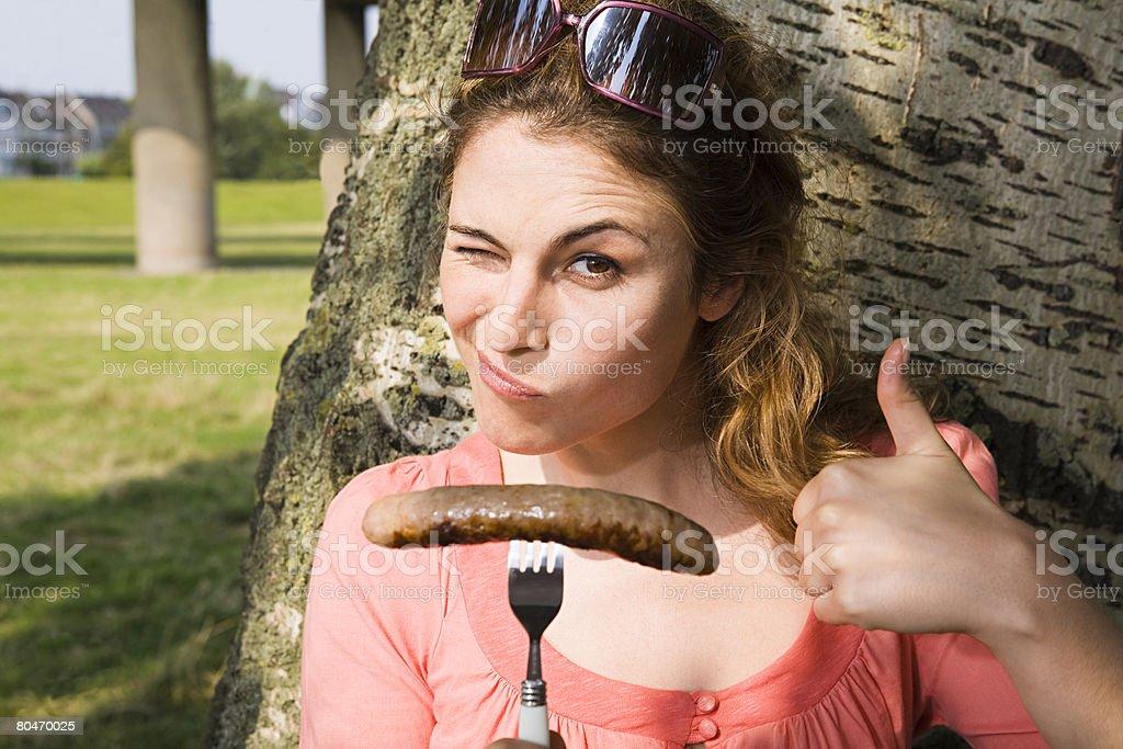 Femme tenant une saucisse et Faire un clin d'oeil - Photo