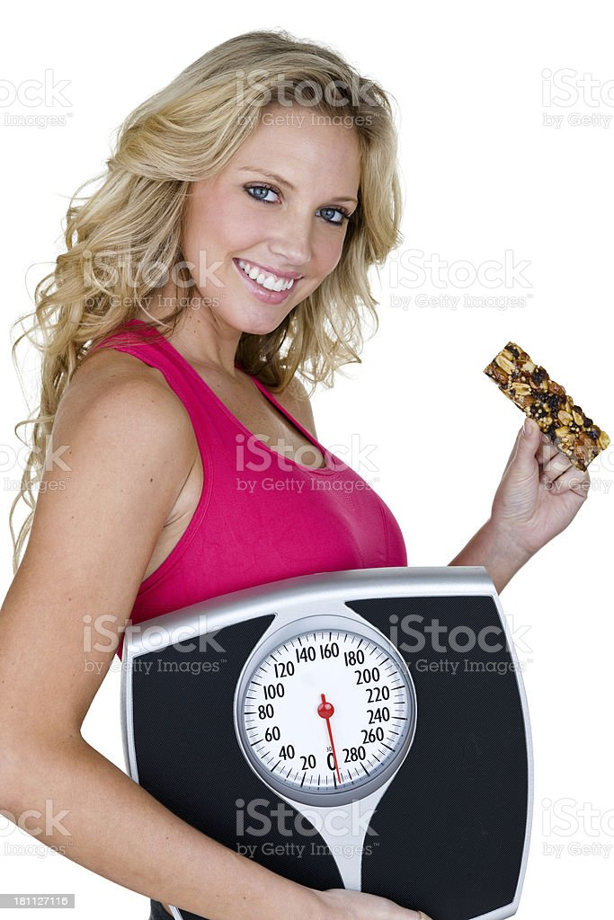 Woman holding a scale and eating healthy royalty-free stock photo