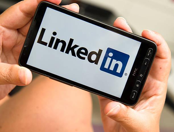 женщина держит смартфон с логотип linkedin - hand holding phone стоковые фото и изображения