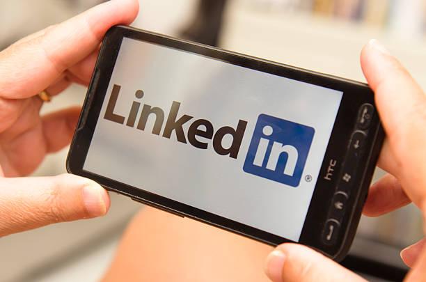 woman holding a smartphone with linkedin logo - linkedin bildbanksfoton och bilder