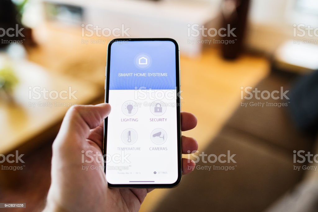 A woman holding a smartphone with smart home screen. stock photo