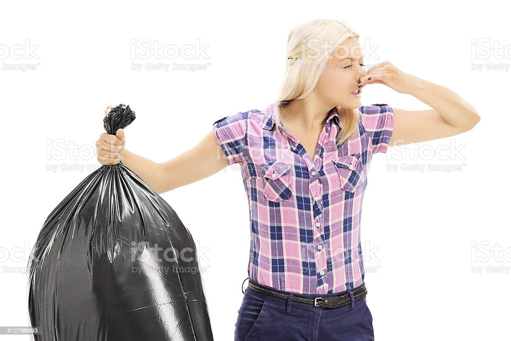 Woman holding a smelly garbage bag stock photo