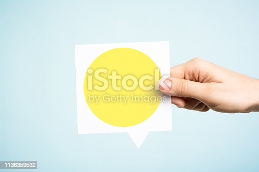 Woman holding a speech bubble with a blank empty yellow circle on blue background. Yellow light concept of traffic light control meaning a warning or wait.