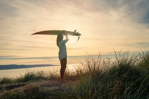 Woman holding a surfboard above her head at sunset, Sand dunes at Gwithian Towan beach, Cornwall.