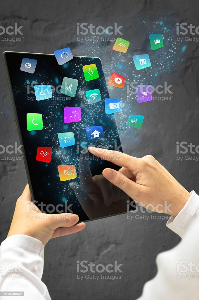 Woman holding a tablet with modern colorfulapps and icons. stock photo