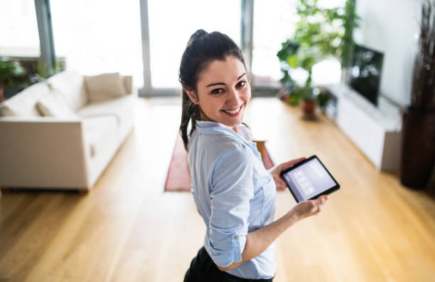 A woman holding a tablet with smart home screen at home. An attractive woman holding a tablet with smart home control system at home. smart thermostat stock pictures, royalty-free photos & images