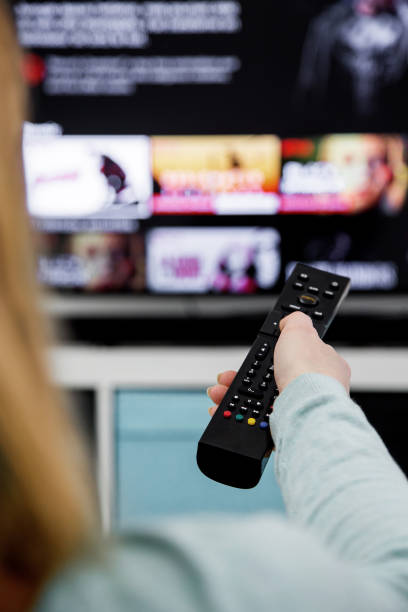 Woman Holding a TV remote control and switching channels on TV set stock photo