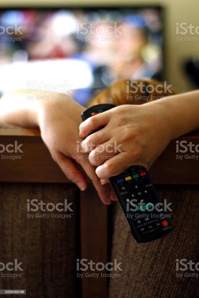 Woman holding a tv remote control stock photo