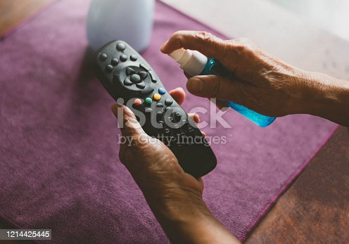 Image of Woman hands with Alcohol Sanitizer and spray on TV remote control prevent the virus and bacterias.