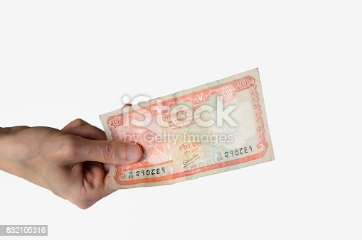 Woman holding a twenty Nepal Rupees banknote in her hand